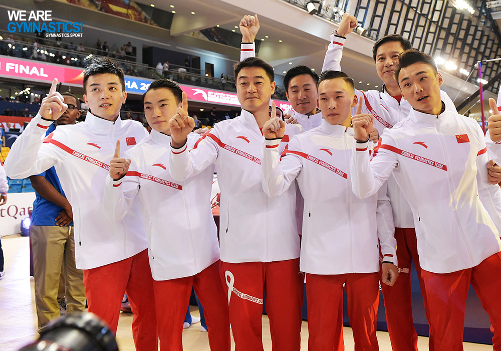 Chinese gymnasts and coaches pose after clinching the men's team title Monday at the 2018 World Championships in Doha (QAT).
